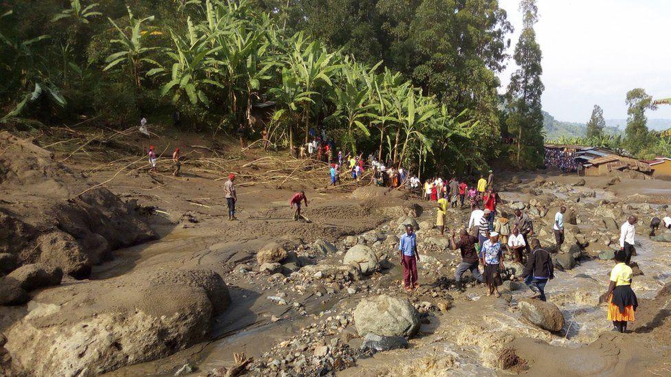 People gather at the scene of a landslide in Bududa area in eastern Uganda,