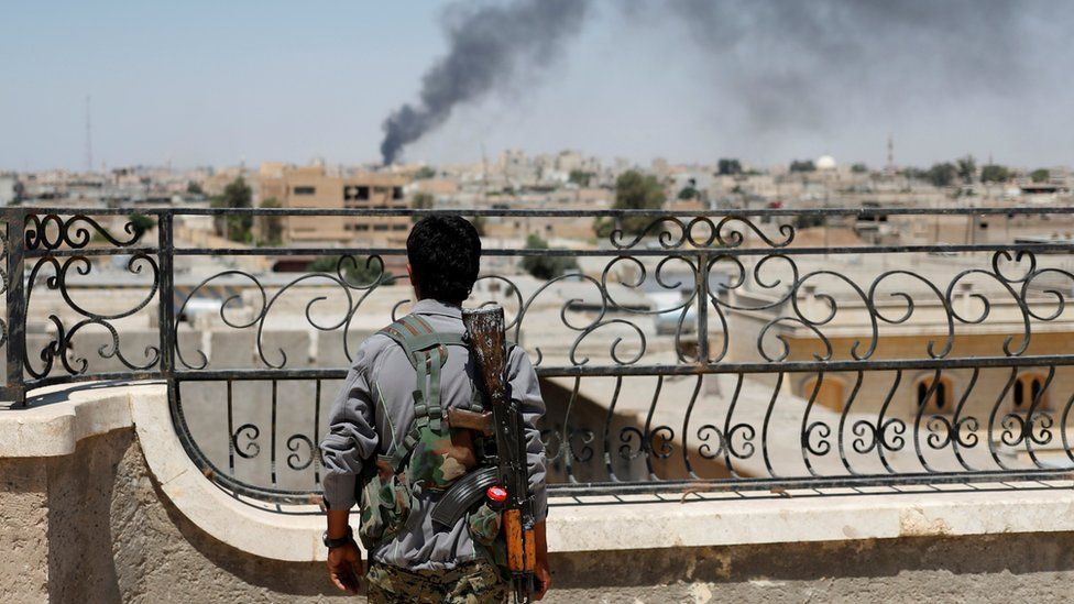 A Kurdish fighter from the People's Protection Units (YPG) looks at a smoke after an coalition airstrike in Raqqa, Syria in June 2016