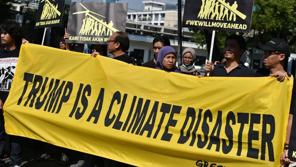 Greenpeace activists display a banner during a rally in front of the US embassy in Jakarta on June 7, 2017