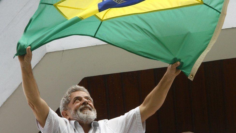 Luiz Inacio Lula da Silva waves a Brazilian flag to supporters from the balcony of his apartment