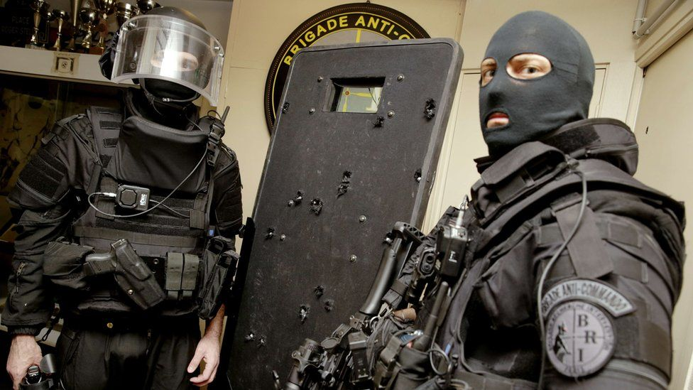French police officers with a shield damaged by many bullets
