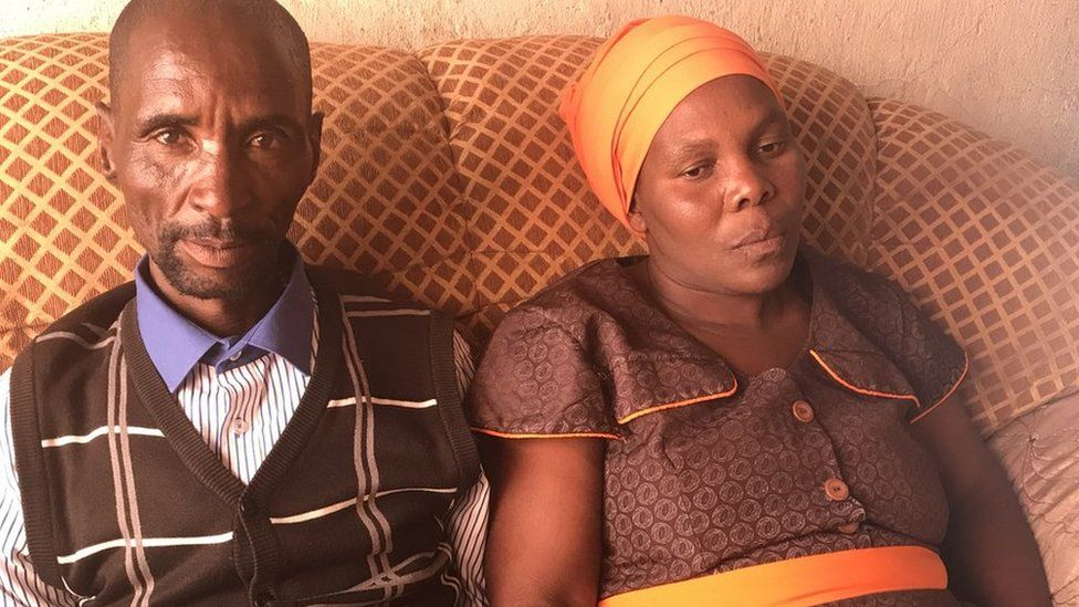 Michael's parents, James Komape and Rosina Komape, sit together on a sofa at their home.