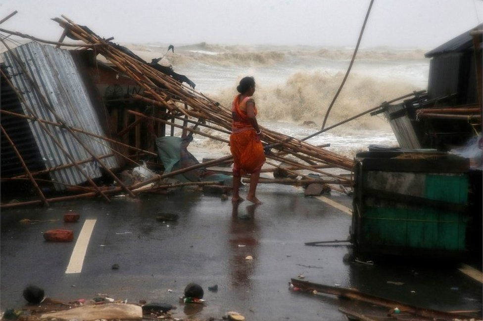 A woman stands next to her stall damaged by heavy winds at a shore ahead of Cyclone Yaas in Bichitrapur in Balasore district in the eastern state of Odisha India, May 26, 2021.