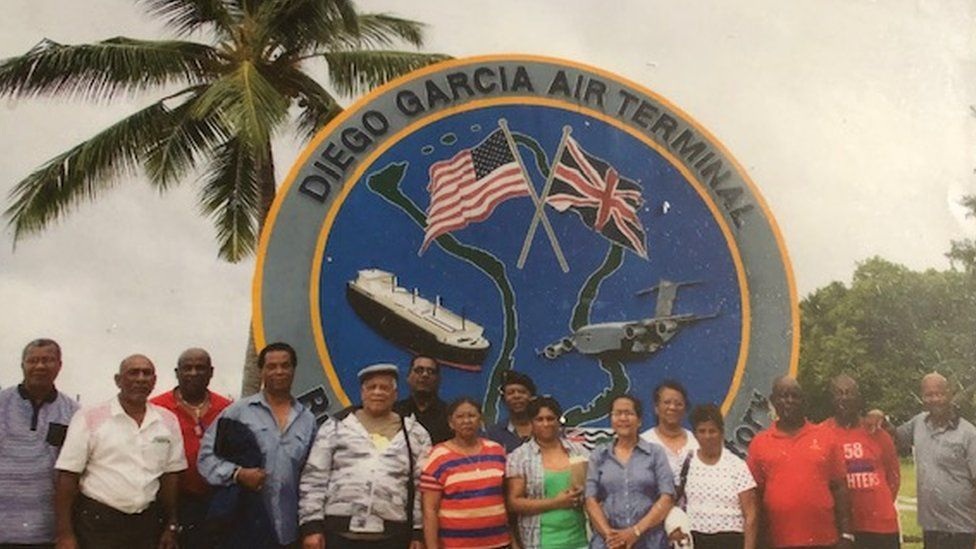 First generation Chagossian exiles standing in front of the military airbase on Diego Garcia