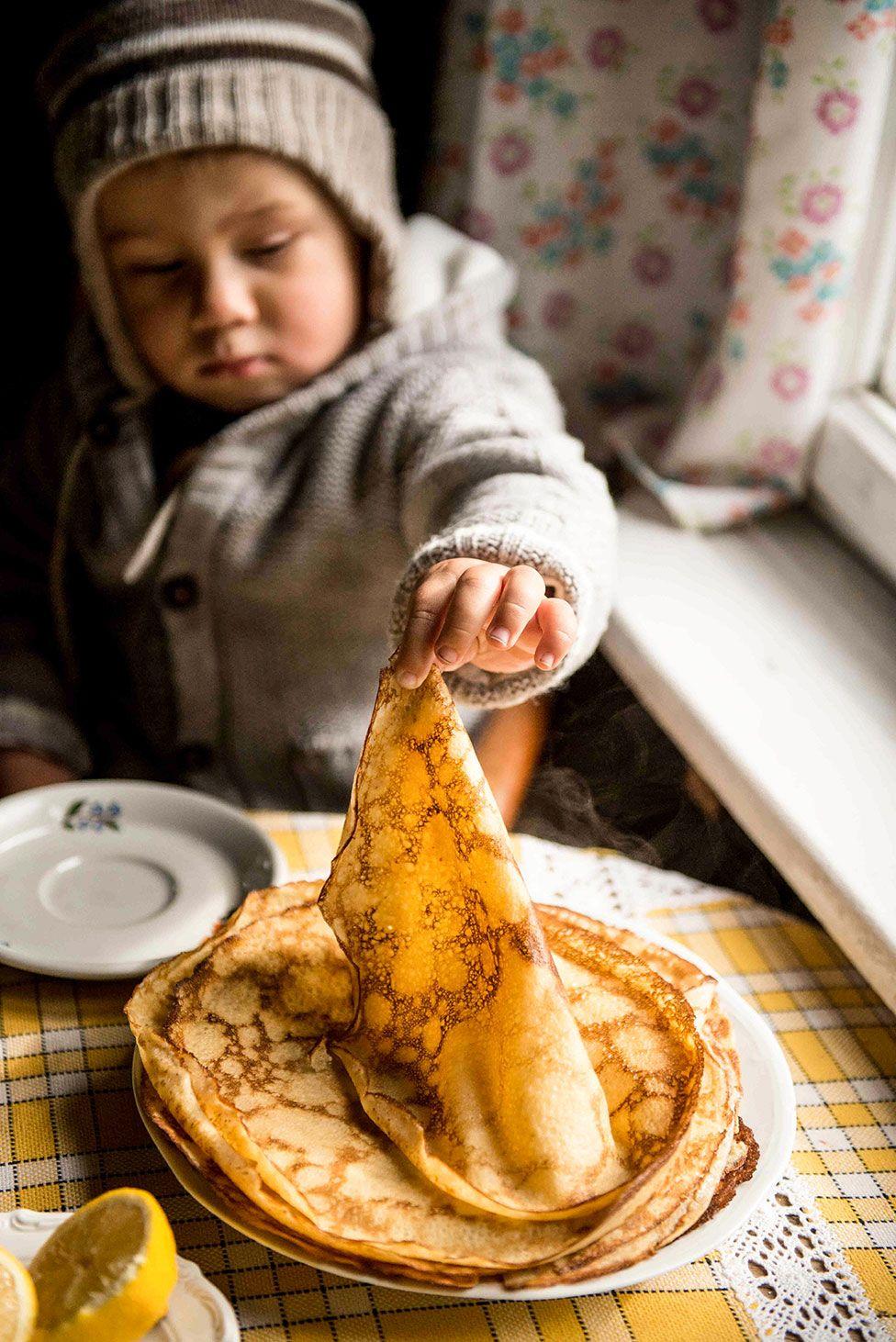 طفل يلتقط فطيرة من طبق