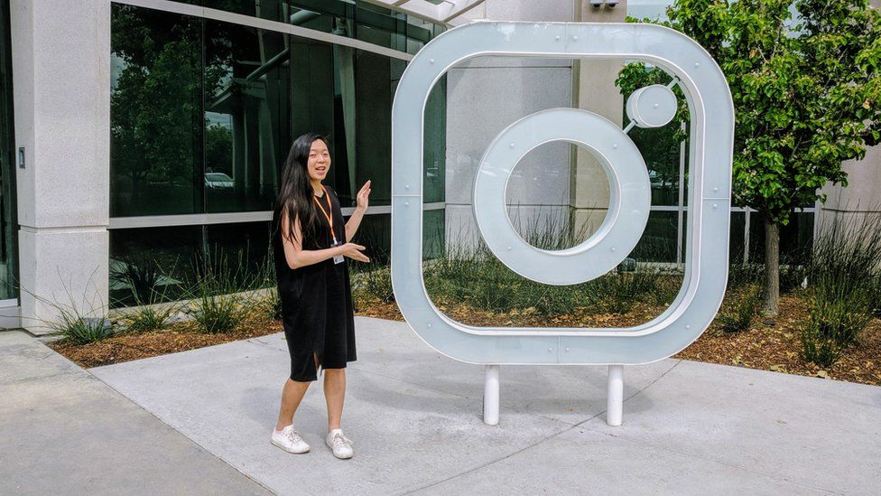 Ms Wong standing next to Instagram logo