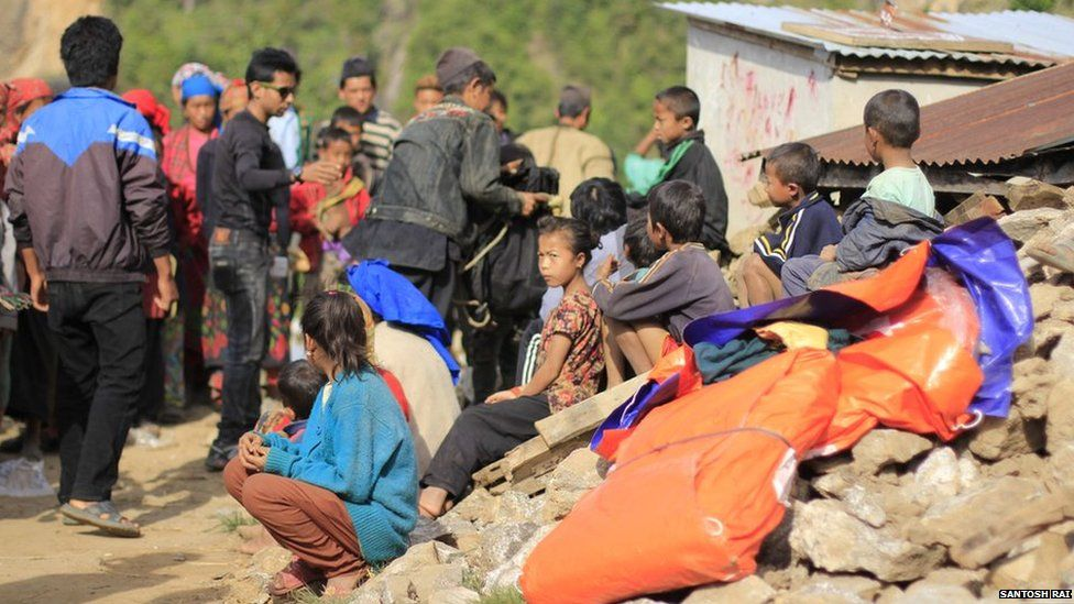 Ajay Pandit Chhetri (in black t-shirt) gives out aid in the team's main project area in remote Shikhar Besi