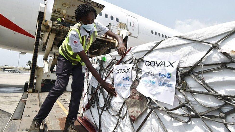 A woman puts on Covax stickers as workers unload a shipment of AstraZeneca Covid-19 vaccines