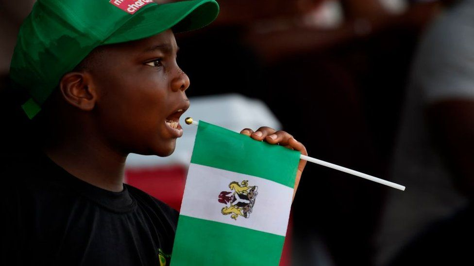 Boy holding a Nigerian flag while watching cricket