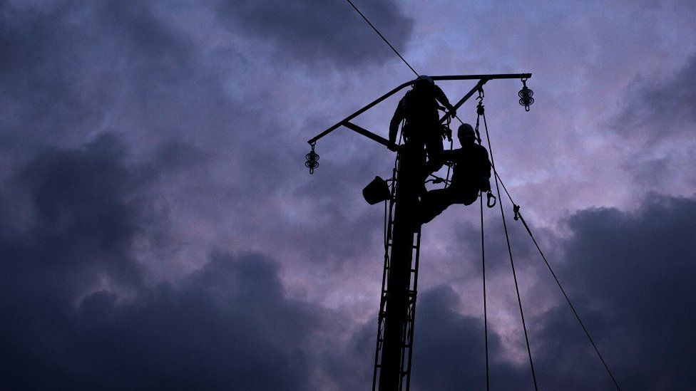 Workmen repairing power lines