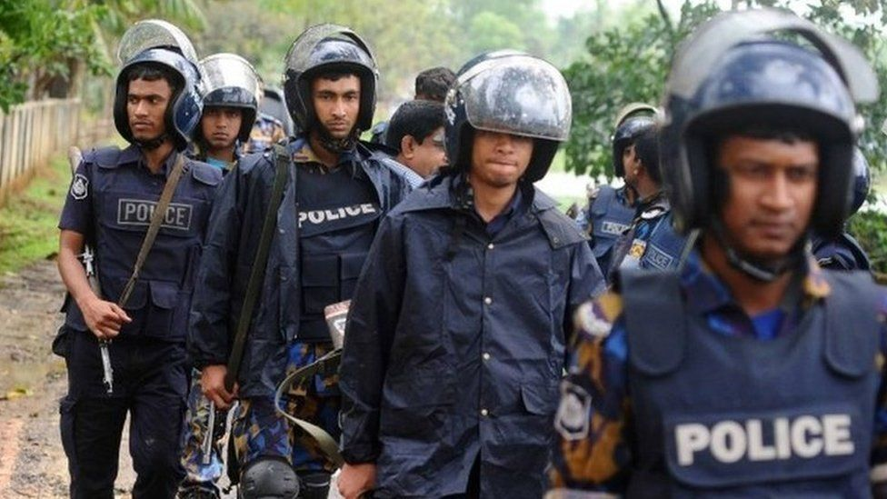 Policemen walk during an operation to storm an Islamist extremist hideout in the town of Moulvibazar on March 30, 2017.