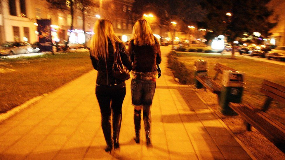 Unidentified young prostitutes walking down a street