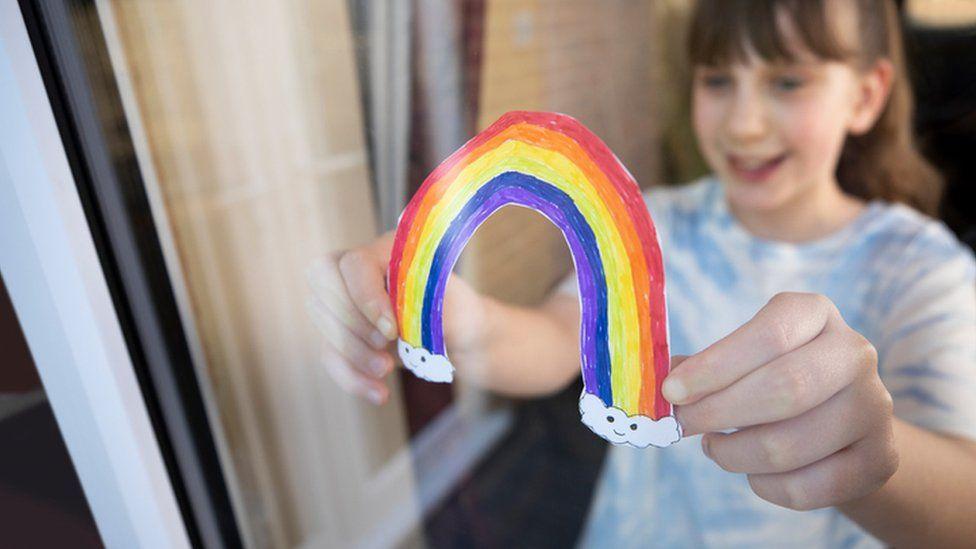 Girl sticks rainbow drawing on window at home