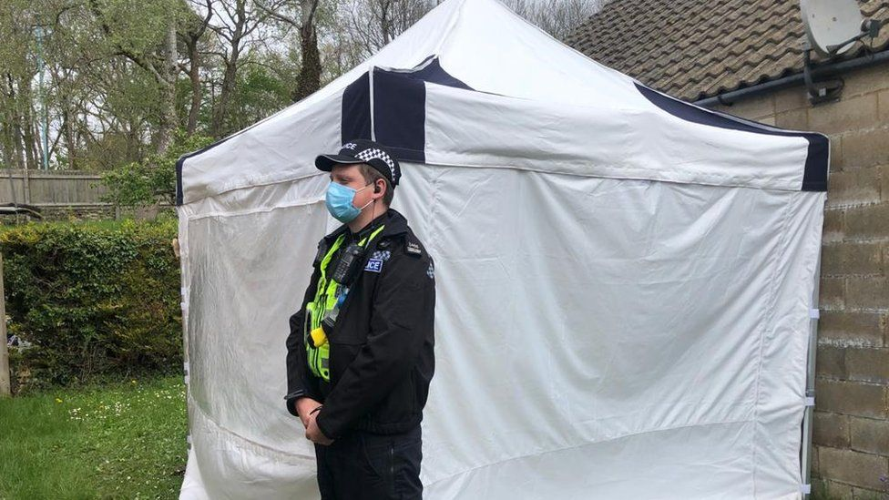 Police officer stands outside crime scene tent
