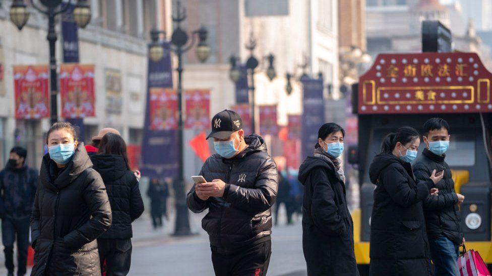 People wearing masks walking on the famous business street of Binjiang Dao, at downtown Tianjin.