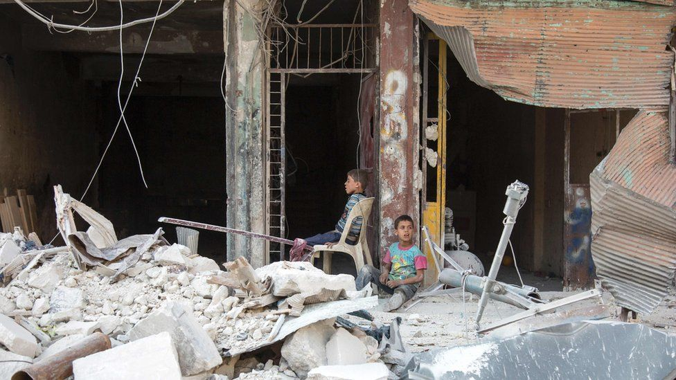 Two boys sit amid the rubble of war-damaged buildings in rebel-held Aleppo (6 July 2016)