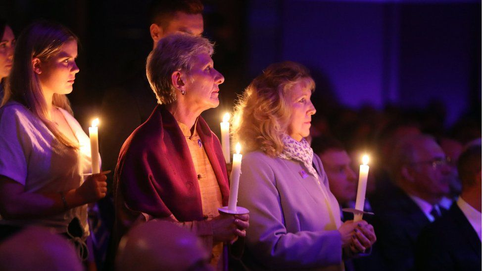 People hold candles during the UK Holocaust Memorial Day Commemorative Ceremony at Central Hall in Westminster, London