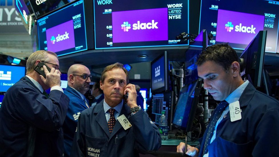 Traders gather around a post as they wait for shares of Slack to start trading