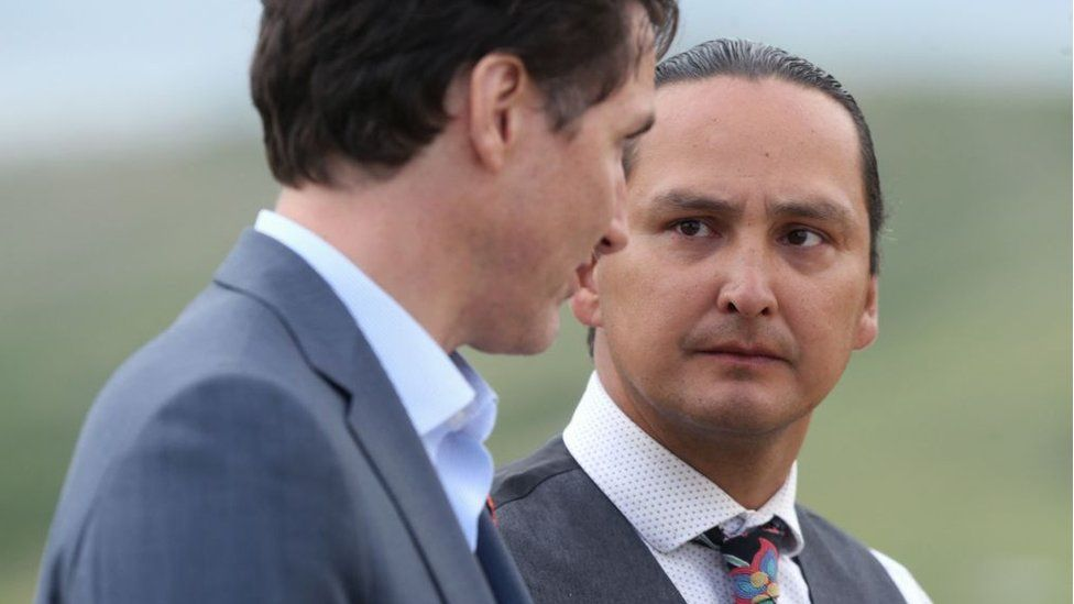 Prime Minister Justin Trudeau (L) speaks to Chief Cadmus Delorme during a visit to Cowessess First Nation