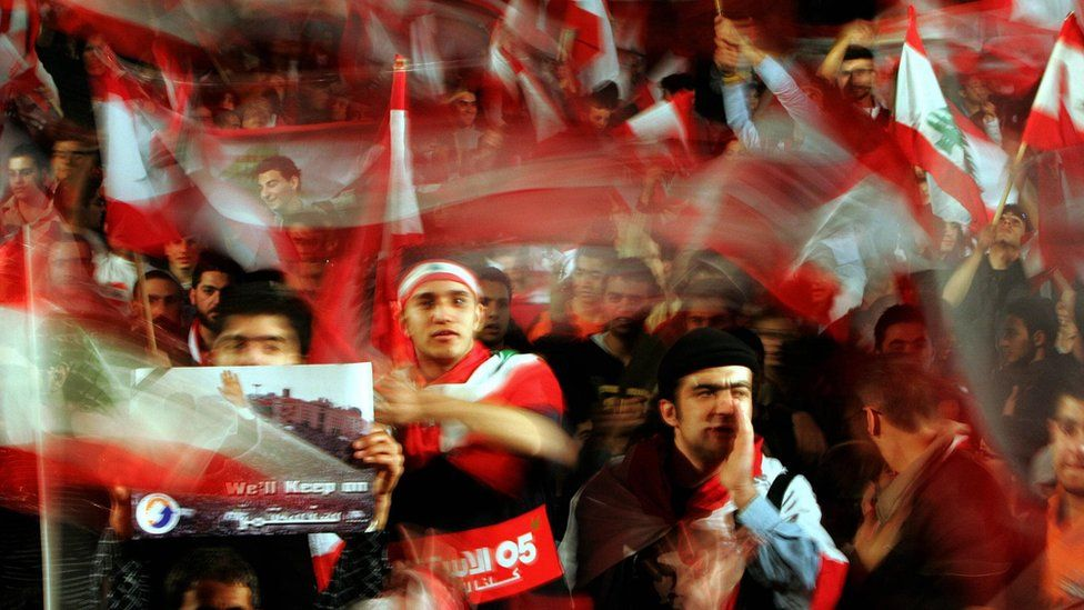 Lebanese opposition supporters wave flags after Bashar al-Assad said Syria would redeploy its troops in Lebanon (5 March 2005)