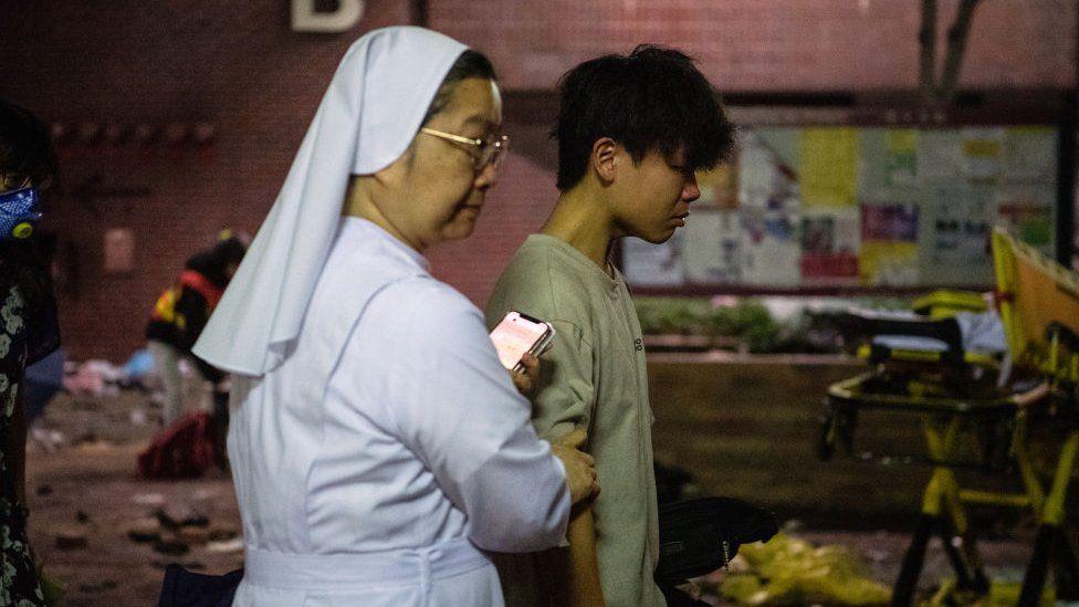 A nun leading a protester out of PolyU