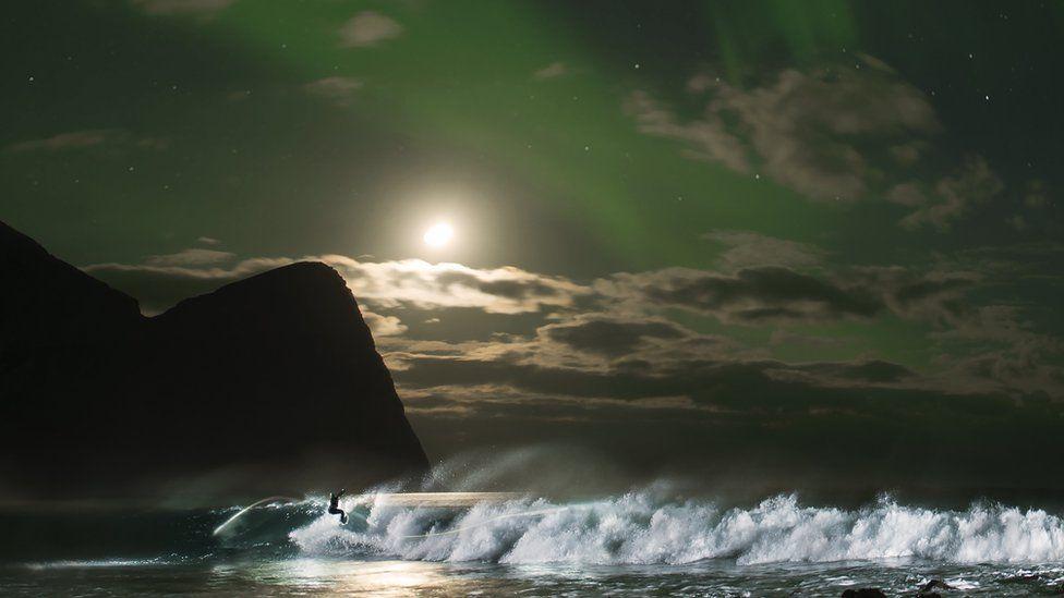Fanning, 35, hit the surf as the Aurora Borealis lit up the archipelago of Lofoten.