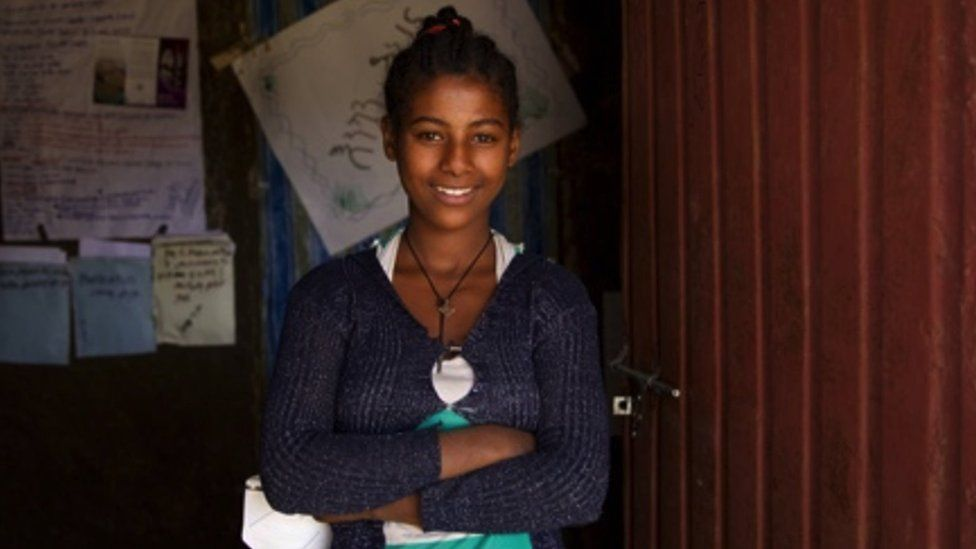 Abeba stands by her school's doors
