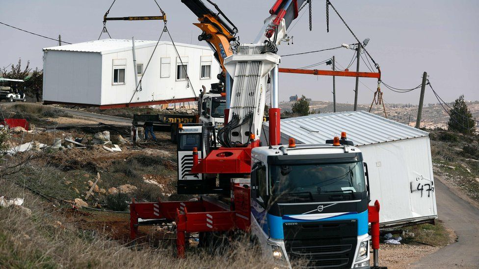 Lorries remove housing units from the unauthorised settlement outpost at Amona