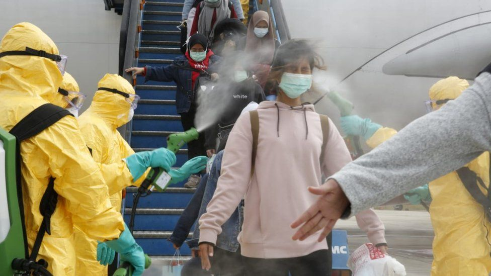 Medical officers spray Indonesian nationals with antiseptic after they arrived from Wuhan