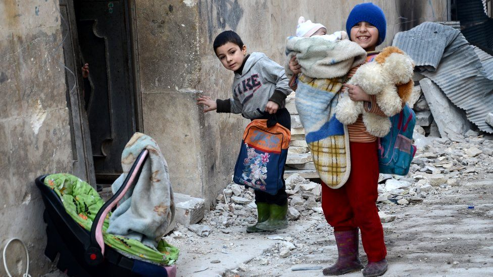 Syrian girl, holding her baby brother, stands next to the rubble