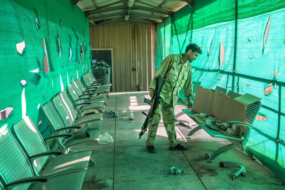 An Afghan army soldier surveys belongings left by the US military inside the Bagram Air Base, some 50 kilometers north of the capital Kabul.