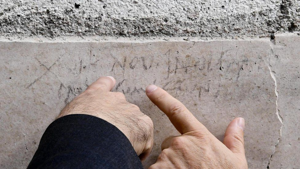 Two men's' hands point to a faded inscription on the stonework of a wall. While mostly incomprehensible to those who do not read ancient Latin, the letters NOV can clearly be seen - a reference to November