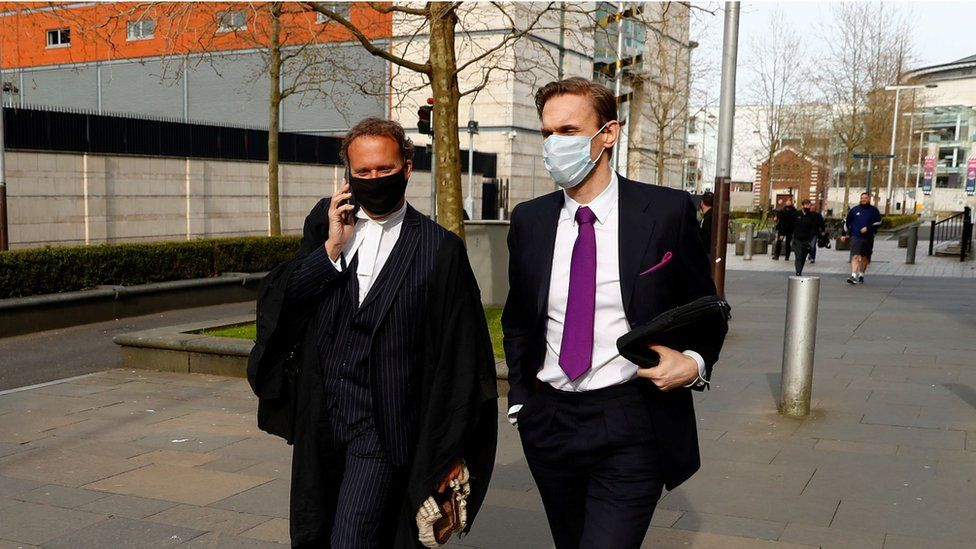 Dr Christian Jessen walks with a lawyer outside the court in Belfast