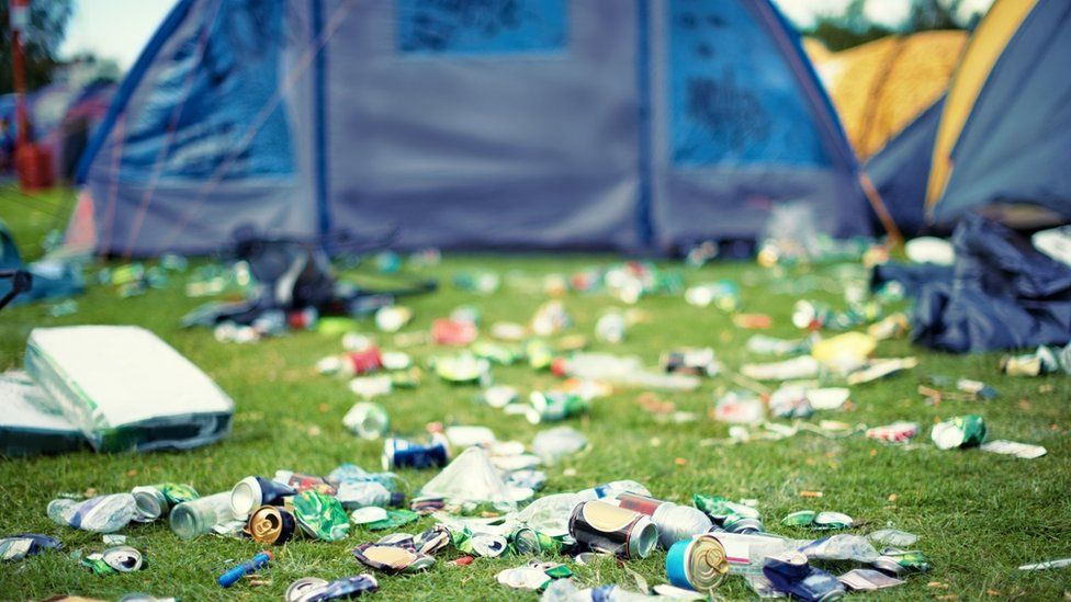 A shot of a festival campsite strewn with litter.