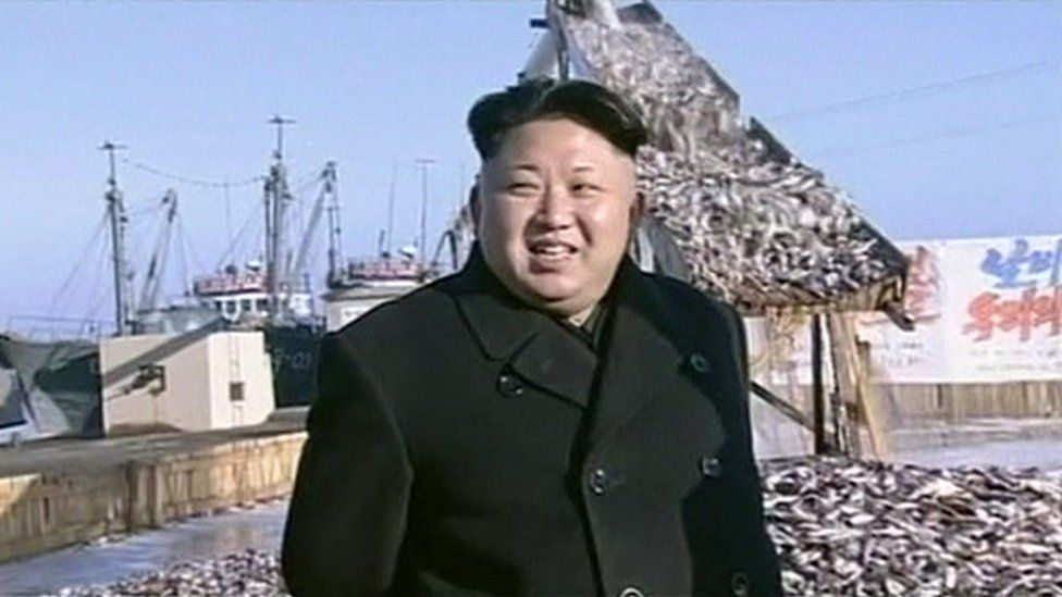 Kim Jong-un in front of a chute down which fish are pouring, in a harbour in North Korea