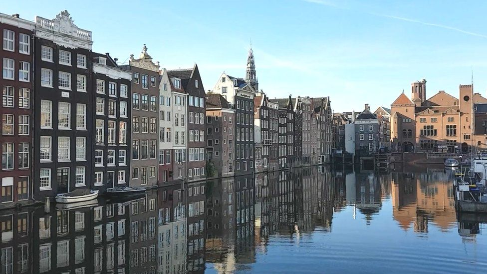 Amsterdam buildings reflected in harbour