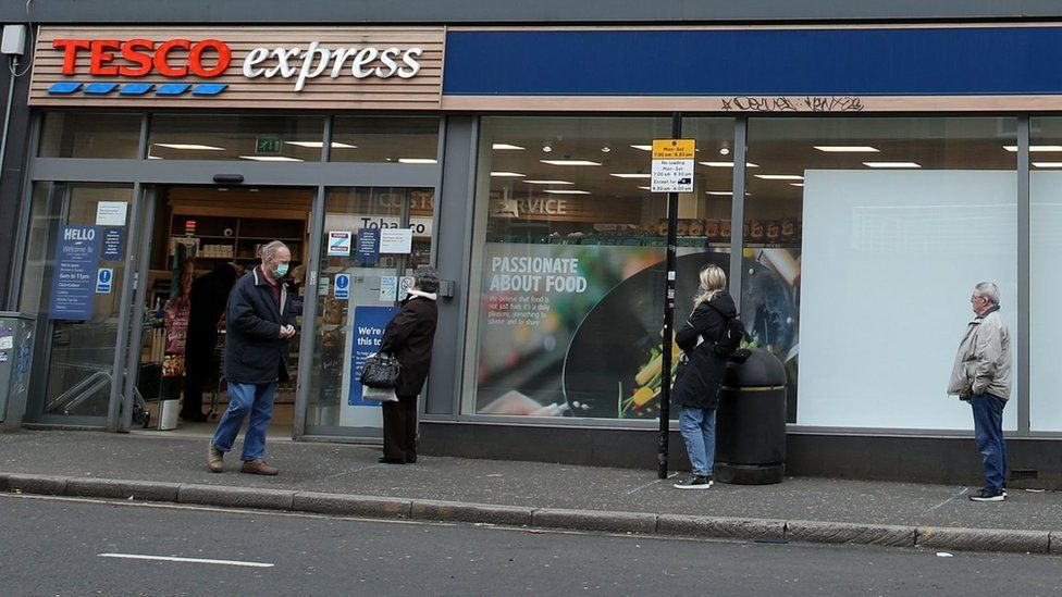 People social distancing outside a Tesco Express in Glasgow