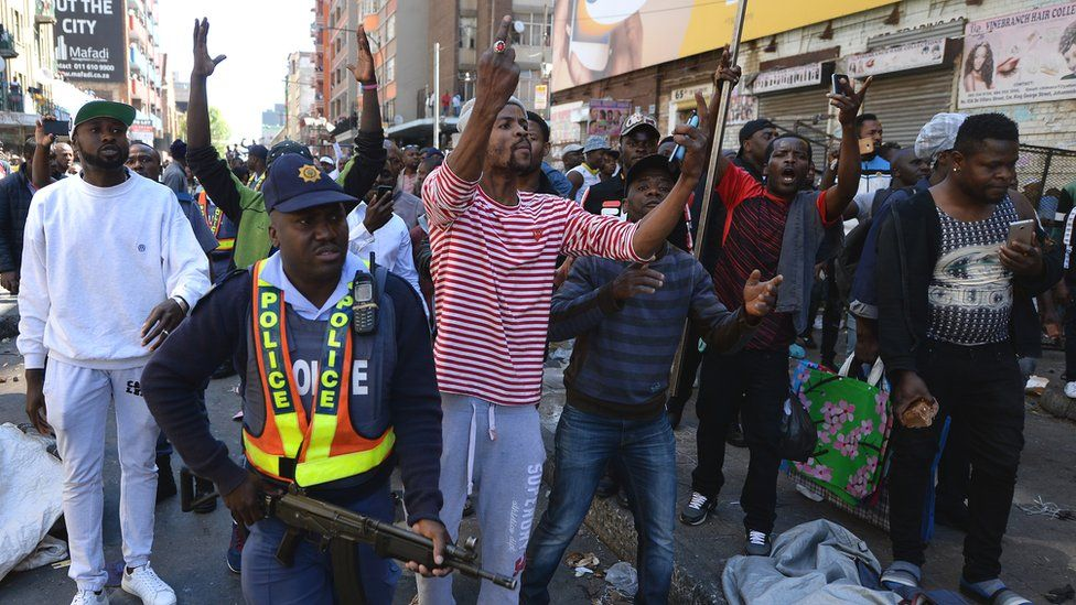 A police officer attempts to quell the violence in Johannesburg