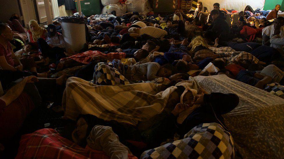 Migrants sleep on board the Vos Prudence