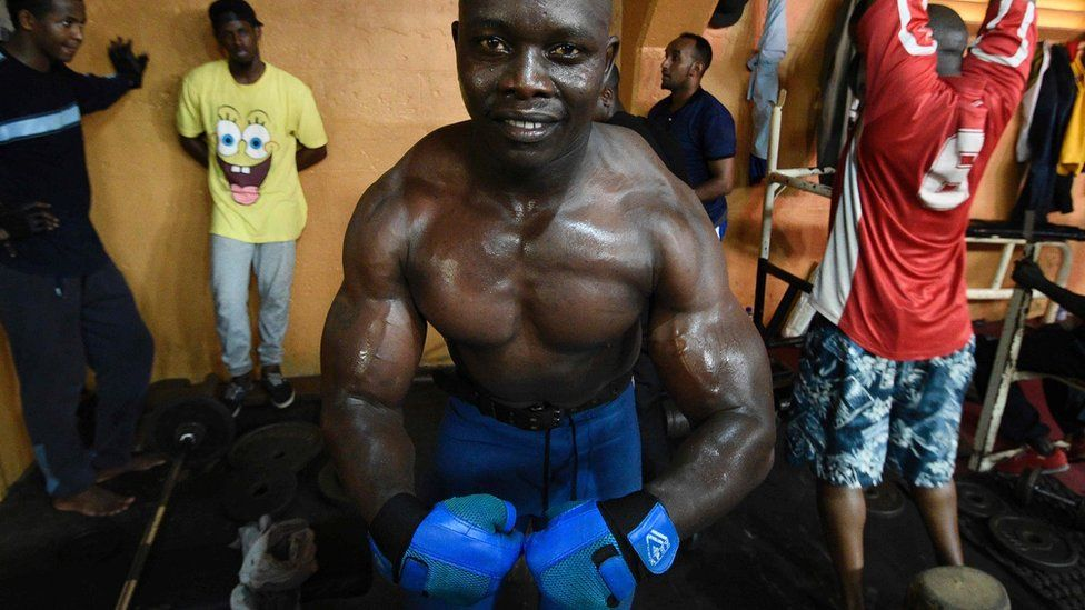 In a Kampala gym, a bodybuilder poses for a picture after lifting weights.