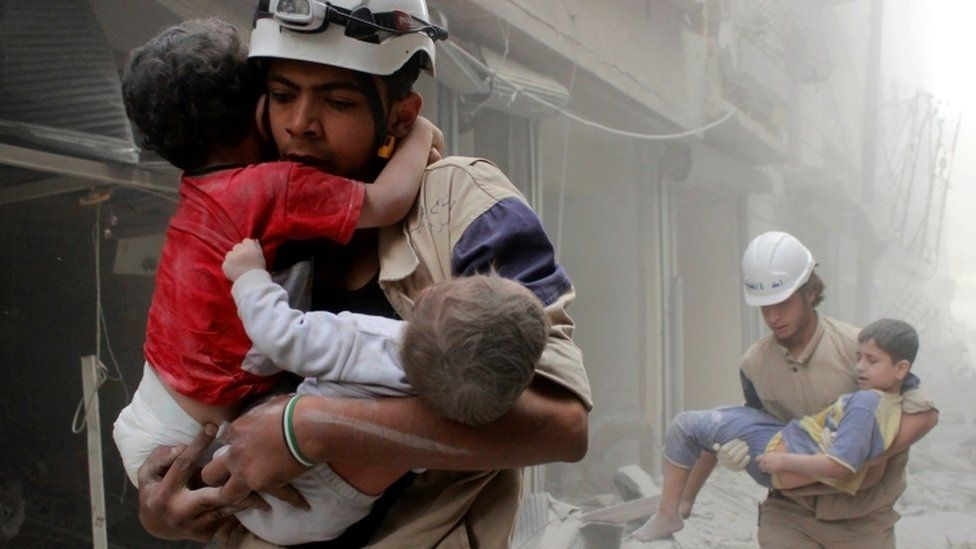 Rescue workers carry children to safety after an airstrike in Syria in Aleppo in 2014