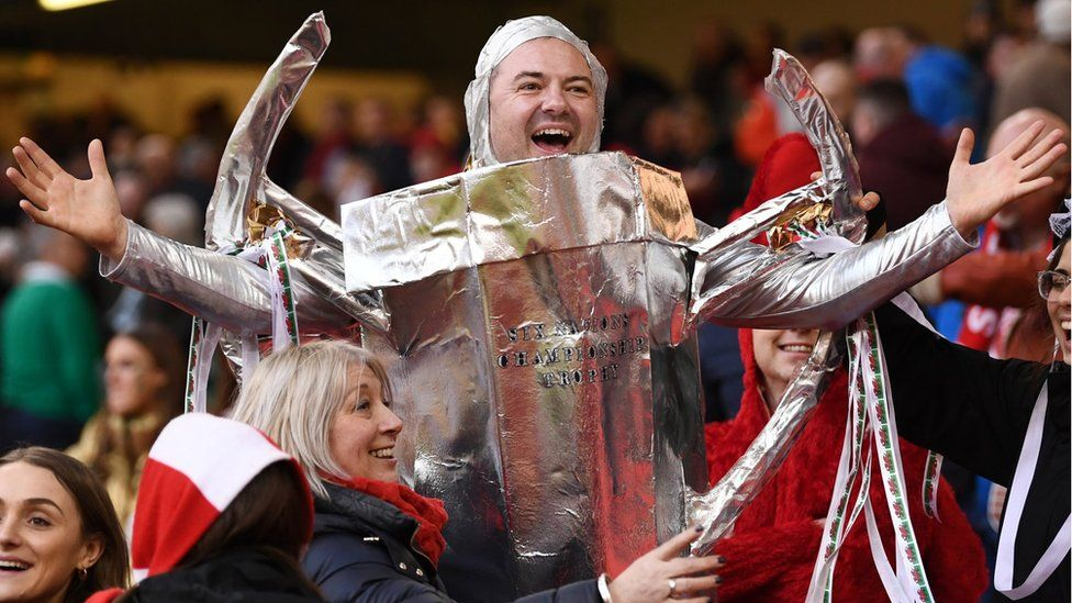 A Wales fan celebrates after Wales' Grand Slam win, dressed as the Six Nations trophy