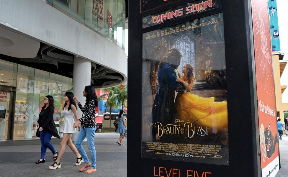 People walk past a poster for the film Beauty and the Beast in Singapore on 14 March 2017.
