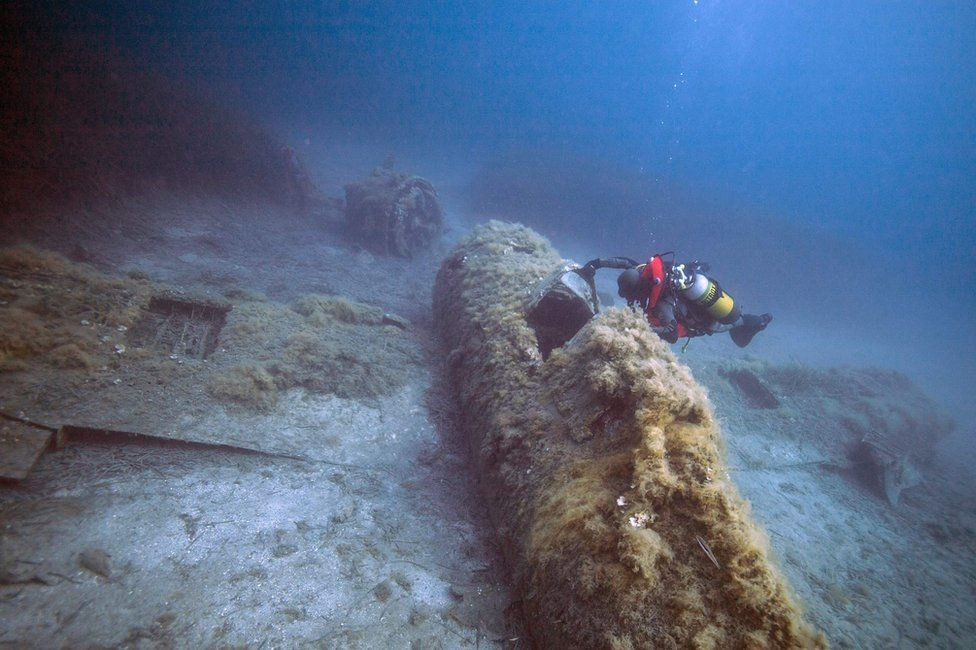 A French military diver member of the FS Pluton M622 navy de-mining ship, swims above the wreck of an USAAF P-47 Thunderbolt (Warthog) US fighter plane