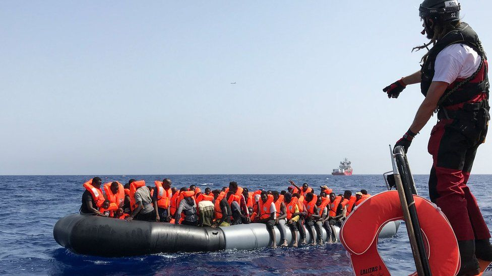 """A crew member of the """"Ocean Viking"""" rescue ship helps migrants in a dinghy on 9 August"""
