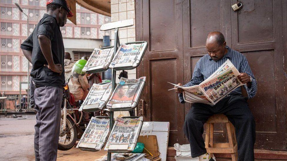 Men reading newspapers at a stall in Kampala, Uganda - 15 January 2021