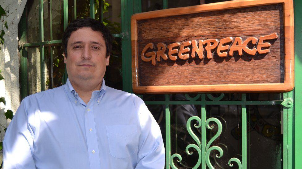 Matías Asún poses next to a Greenpeace sign