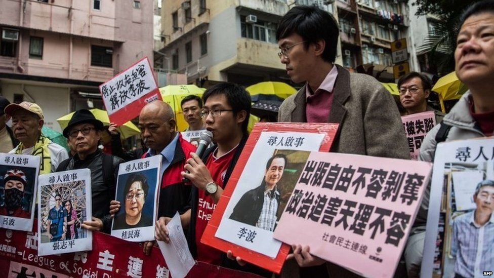 """Protesters hold up missing person notices of (L-R) Mighty Current publisher of books critical of China company""""s general manager Lui Bo and colleagues Cheung Jiping, Gui Minhai, Lee Bo and Lam Wing-kei as they walk towards China""""s Liaison Office in Hong Kong on January 3, 2016."""