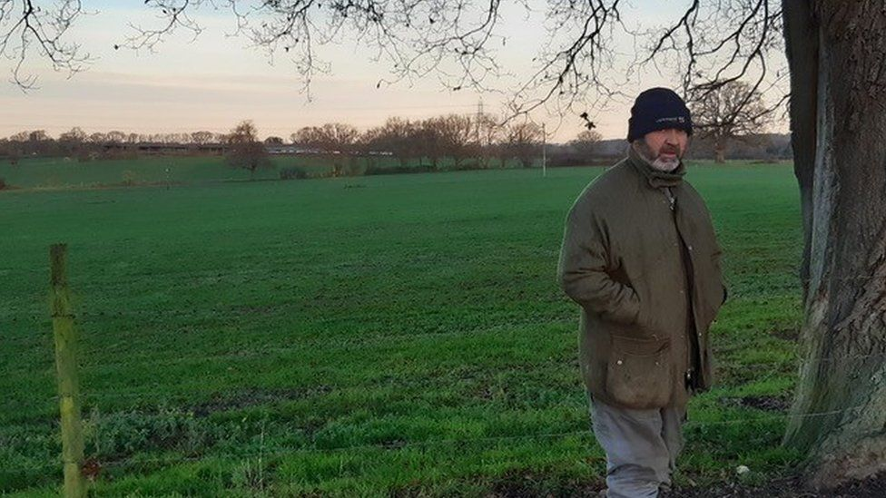 Farmer Andrew Lake standing next to an empty green field