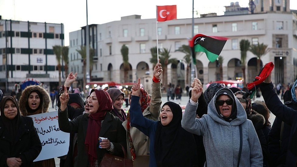 Libyans wave a Turkish and a national flag during a rally in support of the UN-recognised Tripoli-based government (GNA), in the capital Tripoli on January 3, 2020